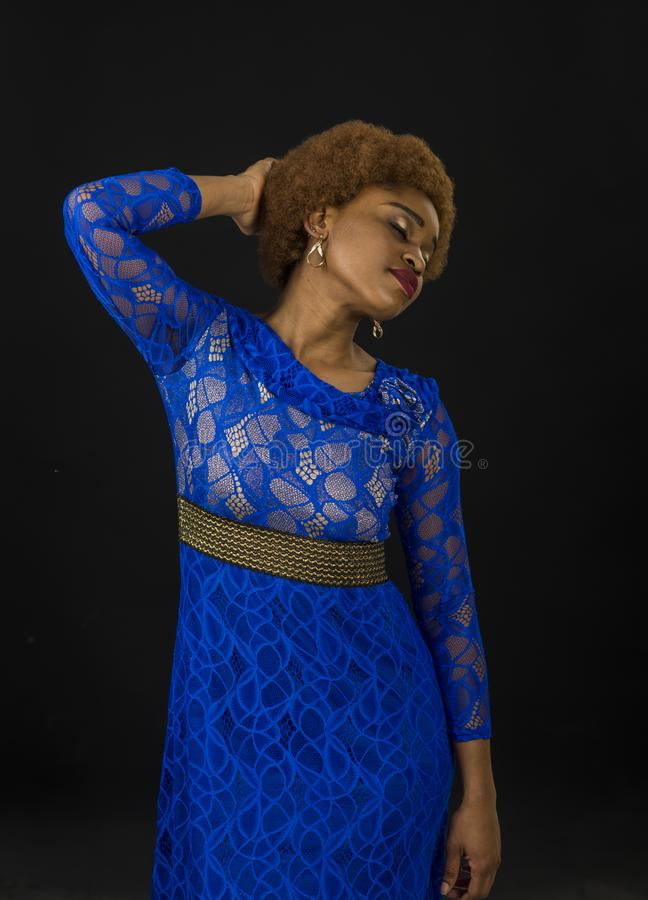 Lady in dress made out of lace. African females beauty concept. Woman with african appearance in blue dress looks. Gorgeous, black background. Lady on relaxed stock photos