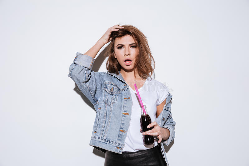 Lady drinking aerated sweet water. Picture of a young lady dressed in jeans jacket standing isolated over white background while drinking aerated sweet water stock images