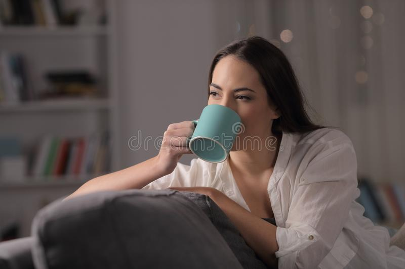 Lady drinking coffee in the night at home royalty free stock images
