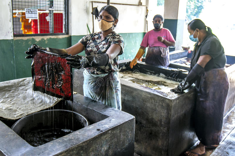 A lady dyeing a batik at the Baba Batik factory near Matale in Sri Lanka. A lady dyeing a batik in chemical vats at the Baba Batik factory near Matale in Sri stock photos