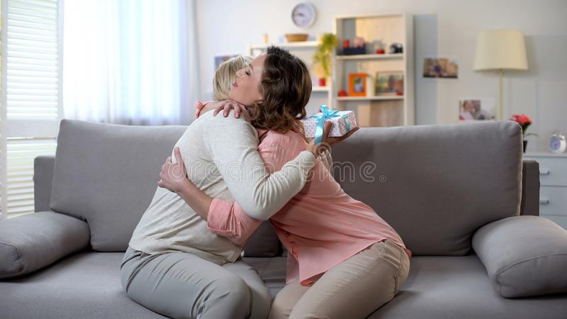 Lady embracing mother, senior woman holding gift box, pleasant surprise, care. Lady embracing mother, senior women holding gift box, pleasant surprise, care stock photo