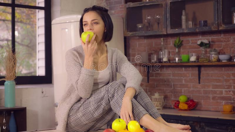 Lady enjoy healthy food at home kitchen. Portrait young woman relish healthy fruit diet. Smiling woman eats fresh apple in loft apartment. Casual female with stock images