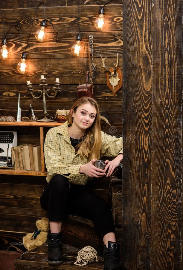 Lady enjoy hot drink in metallic mug in warm atmosphere, wooden interior. Girl on relaxed face in plaid clothes relaxing stock photo