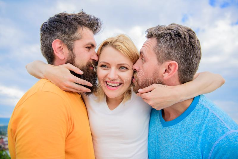 Lady enjoy romantic relations both admirers. She likes male attention. Love triangle. Men fall in love with same woman. Men kiss same girl cheeks. Girl hugs stock image
