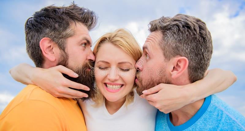 Lady enjoy romantic relations both admirers. Men fall in love with same woman. She likes male attention. Love triangle. Girl hugs with two guys. Romantic stock photography