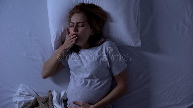 Lady expectant lying in bed feeling nausea, morning sickness, pregnancy health. Stock photo stock images