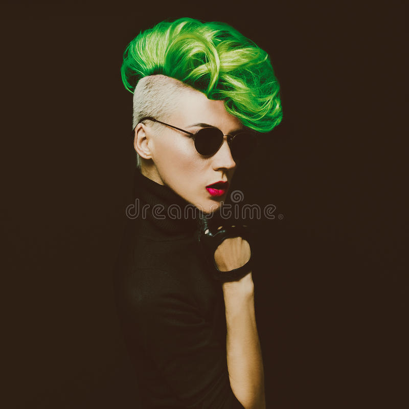 Lady with fashionable haircut Colored hair on a black background. Punk style royalty free stock photography