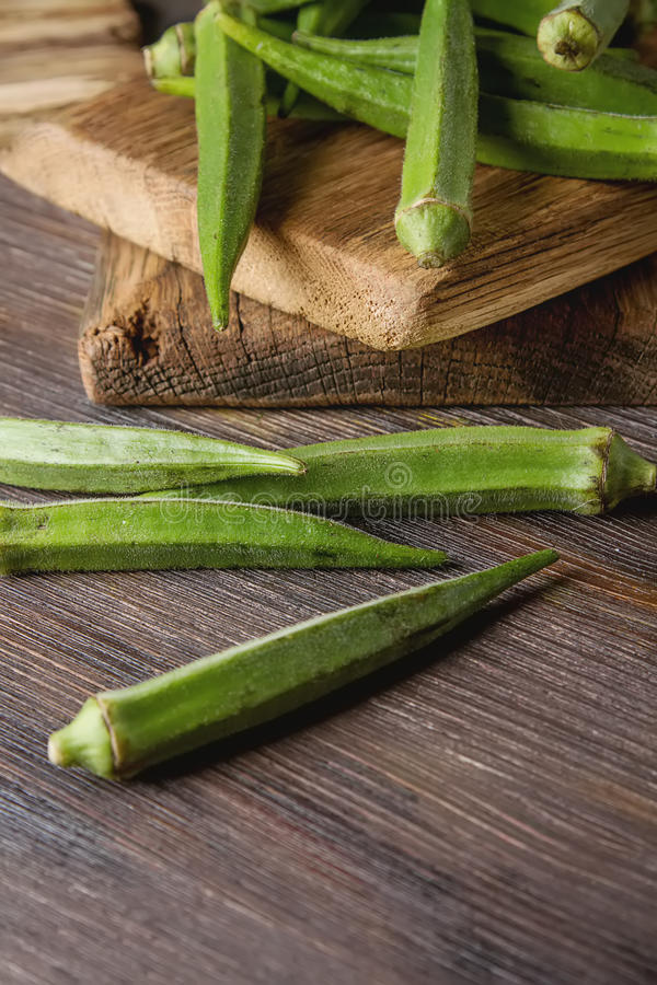 Lady Fingers or Okra over wooden table background. stock photo
