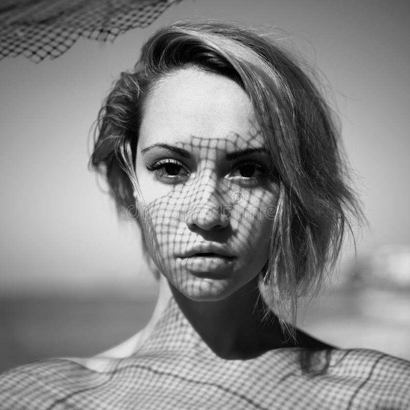 Lady with fishnet pattern on face. Beautiful young lady with a delicate fishnet pattern on face stock image