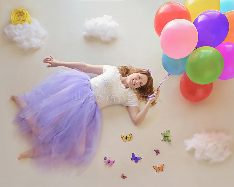 Lady flying with balloons. A fun photo of a lady flying away with colorful balloons royalty free stock photography