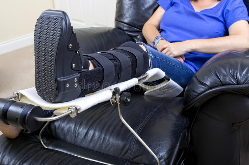 Lady with Fractured Leg. A lady with a fractured leg sat in an armchair with her injured leg in an orthopeadic boot supported on a raised leg support royalty free stock photo