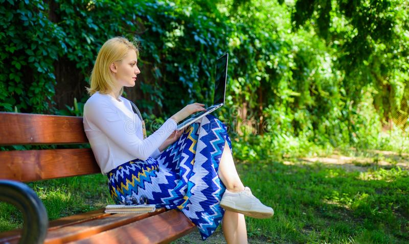 Lady freelancer working in park. Freelance benefits. Woman with laptop works outdoor, green nature background royalty free stock photography