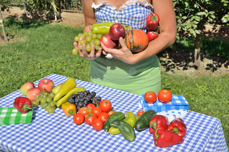 Lady in the garden. Dressed in cottage style, holding different sorts of fruits and vegetables. Photo symbolizes fruitfulness of the end of summer royalty free stock photo