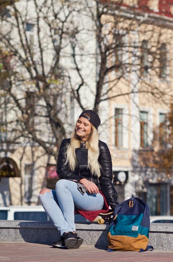 Lady girl happy smiles, sits skateboard stock photos