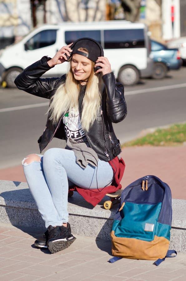 Lady girl happy smiles, sits skateboard royalty free stock photos