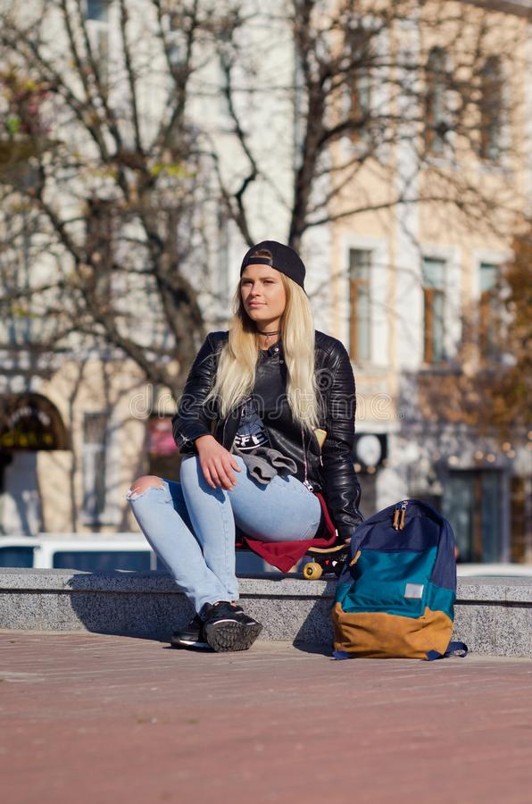 Lady girl happy smiles, sits skateboard stock image