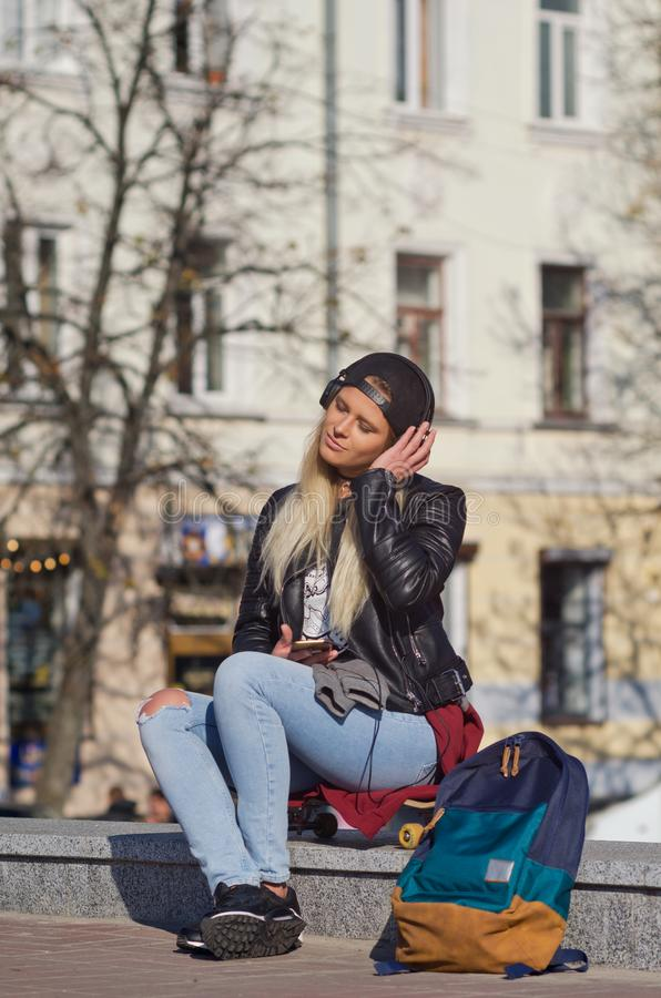 Lady girl happy smiles, sits skateboard stock photography