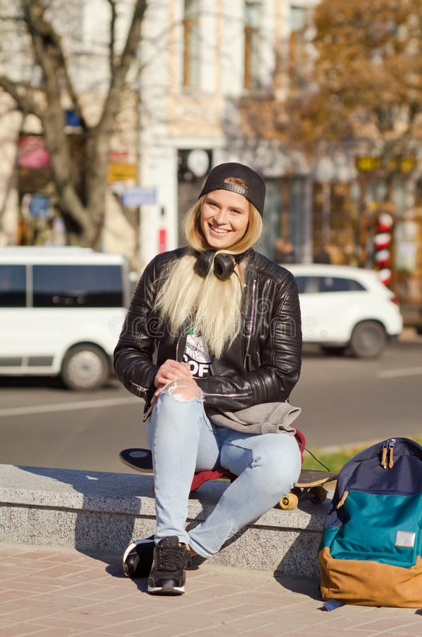 Lady girl happy smiles, sits skateboard royalty free stock images