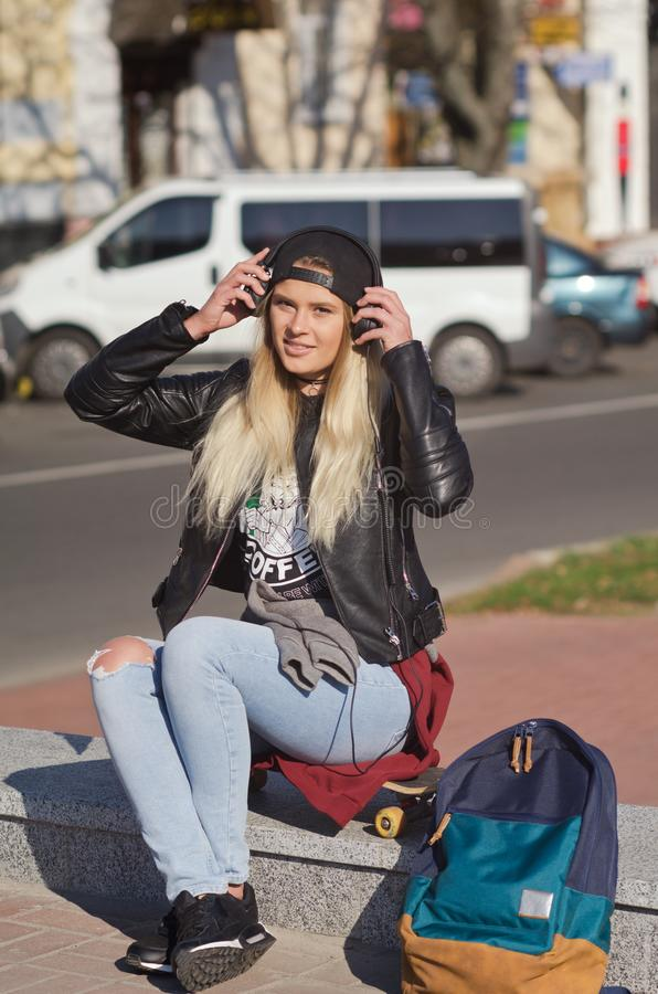 Lady girl happy smiles, sits skateboard royalty free stock image