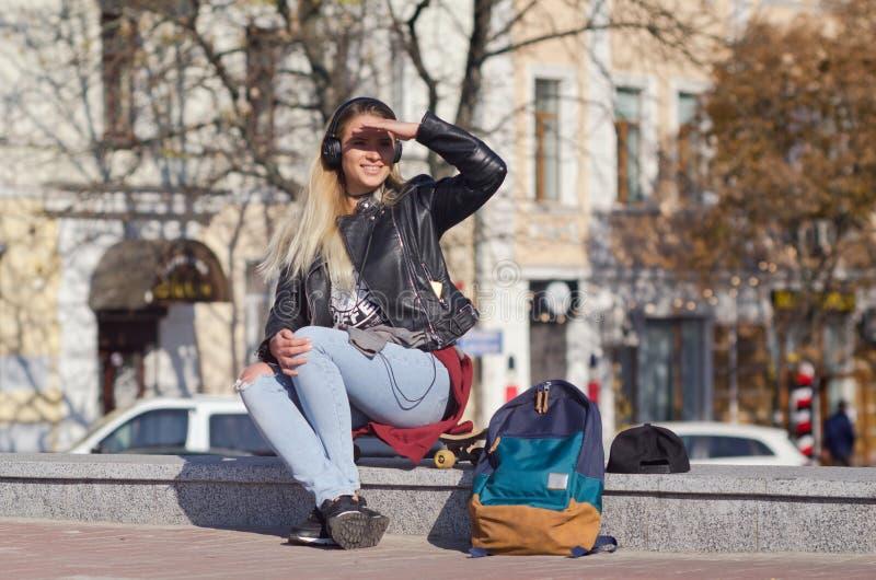 Lady girl happy smiles, sits skateboard royalty free stock photo