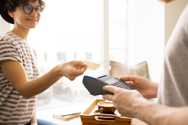 Lady giving credit card to cashier stock images