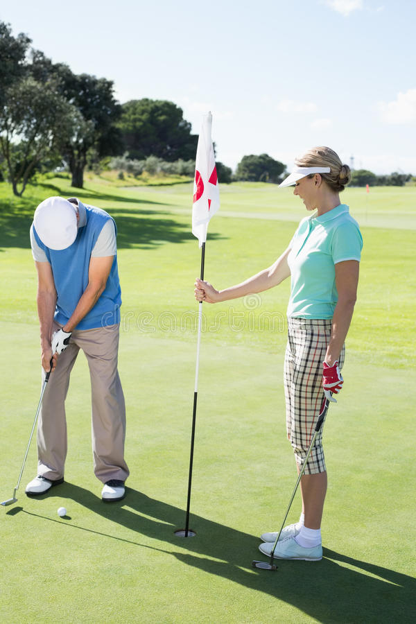 Lady golfer holding eighteenth hole flag for partner putting ball stock images