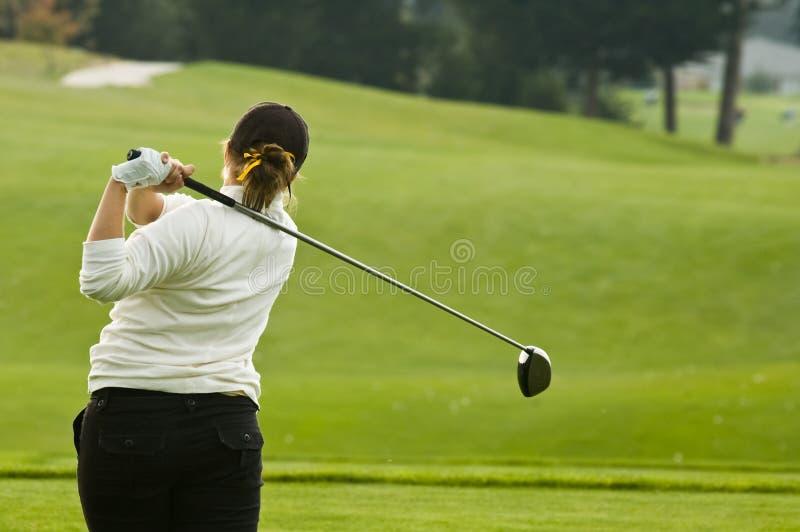 Lady golfer swinging driver royalty free stock photo
