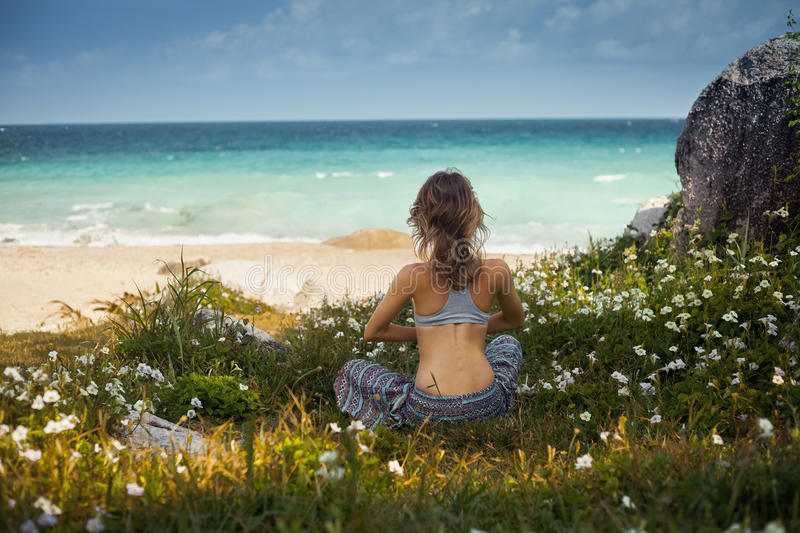 Lady on the grass. Lady sitting on the grass near ocean and doing yoga exercise royalty free stock photography