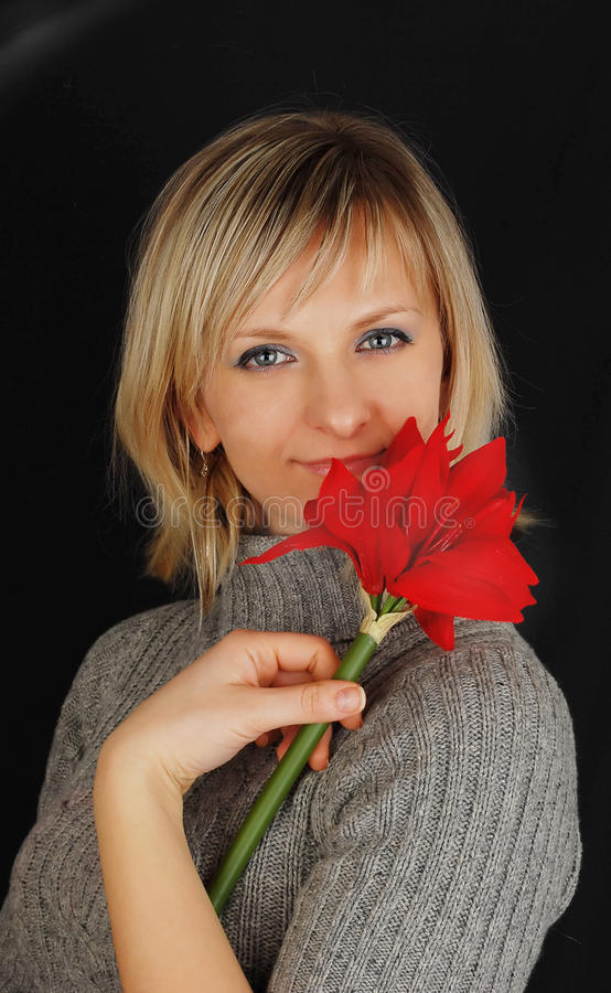 Lady in gray dress with red flower on black. stock images