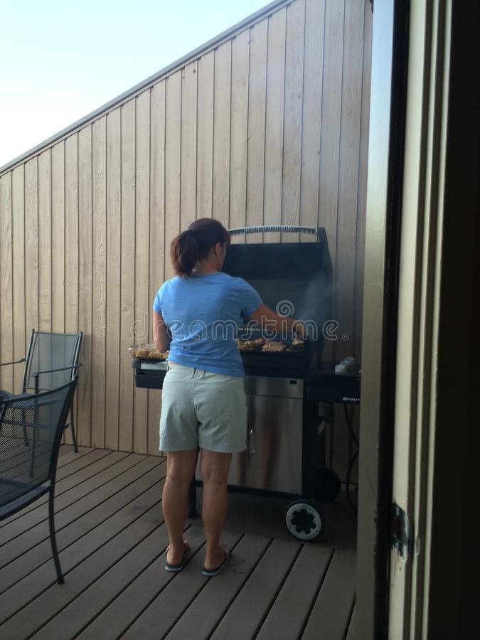 Lady grilling. A woman grilling some chicken royalty free stock image