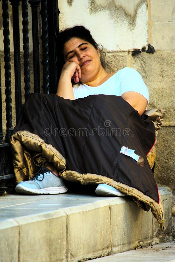 Lady half sleeping in the street. Seville royalty free stock images