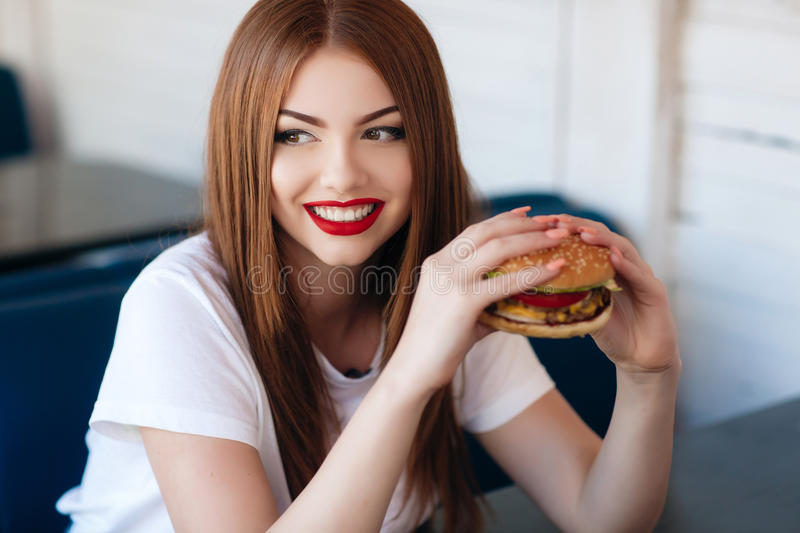 Lady with a hamburger for a table in a cafe. Beautiful woman with red long straight hair, bright make-up, brown eyes, red lipstick, long eyelashes, pink nail stock photography