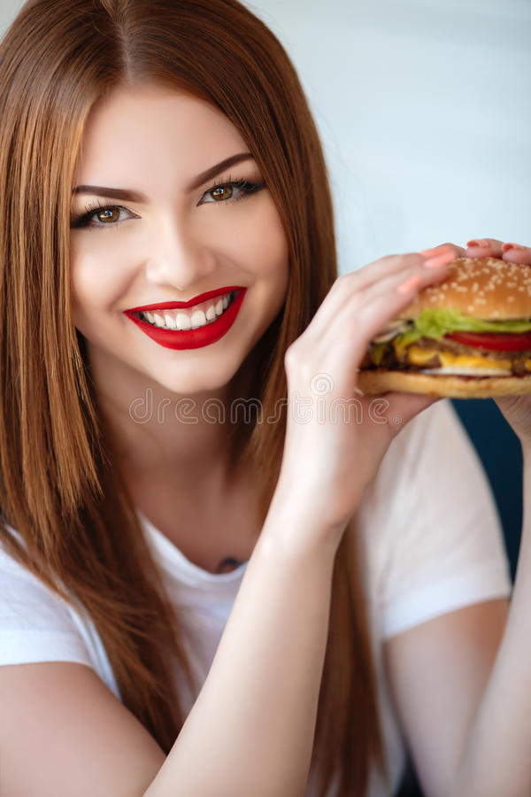 Lady with a hamburger for a table in a cafe. Beautiful woman with red long straight hair, bright make-up, brown eyes, red lipstick, long eyelashes, pink nail royalty free stock photos