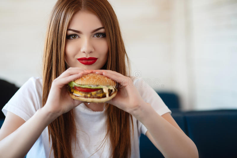 Lady with a hamburger for a table in a cafe. Beautiful woman with red long straight hair, bright make-up, brown eyes, red lipstick, long eyelashes, pink nail royalty free stock photography