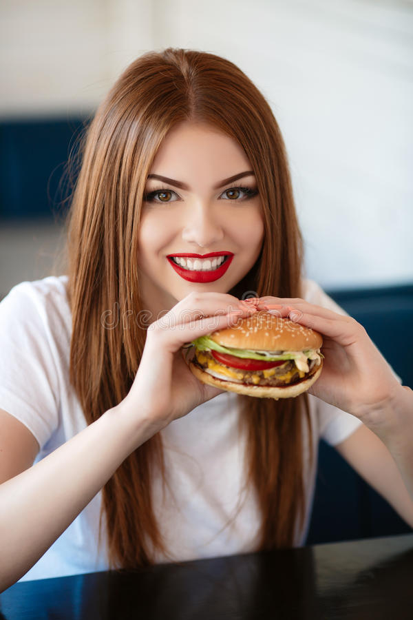 Lady with a hamburger for a table in a cafe. Beautiful woman with red long straight hair, bright make-up, brown eyes, red lipstick, long eyelashes, pink nail royalty free stock images