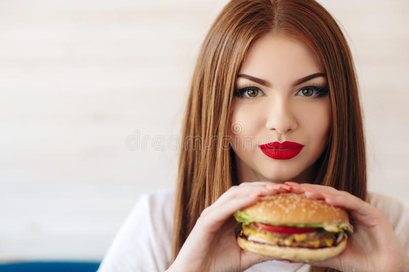 Lady with a hamburger for a table in a cafe. Beautiful woman with red long straight hair, bright make-up, brown eyes, red lipstick, long eyelashes, pink nail royalty free stock image