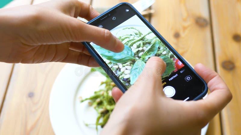 Lady hands make photo of tasty vegetarian salad closeup stock images