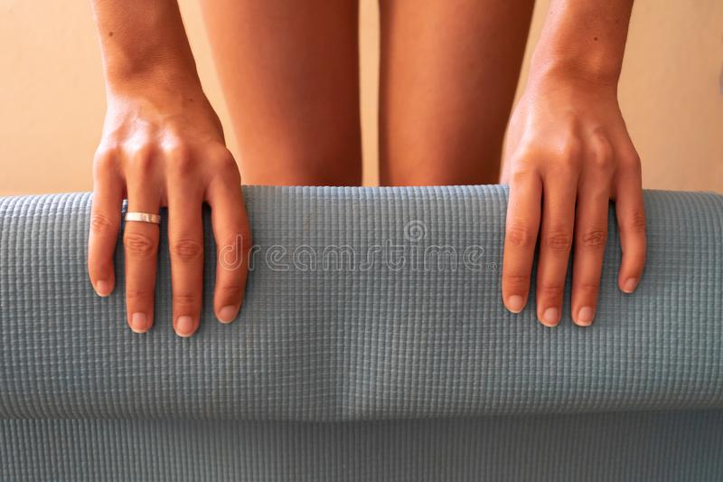 Lady hands rolling a yoga mat after a class of meditation and pilates. Wellness workout and session royalty free stock photo