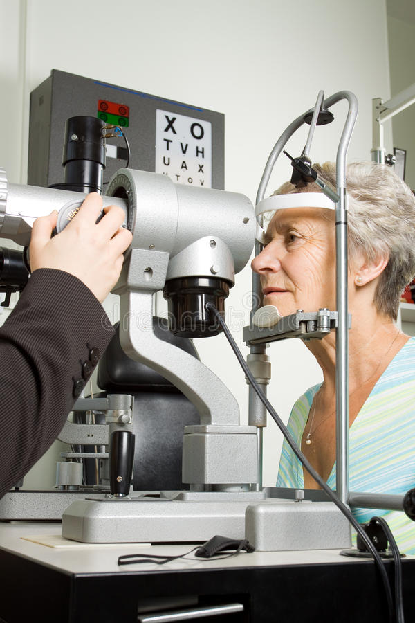 Lady having eye test examination. An older lady taking an eyesight test examination at an optician clinic royalty free stock images