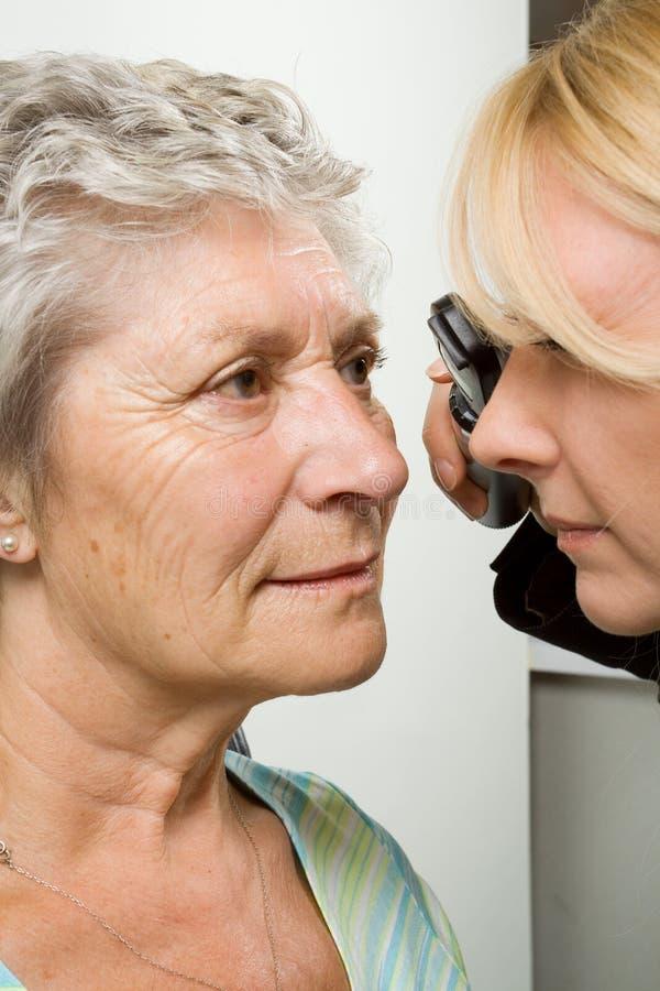 Lady having eye test examination. An older lady taking an eyesight test examination at an optician clinic royalty free stock image