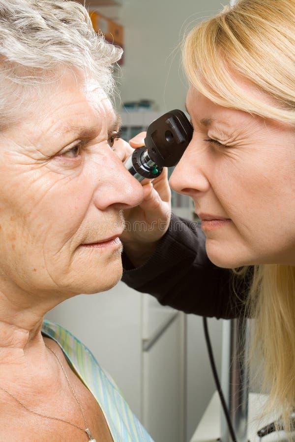 Lady having eye test examination. An older lady taking an eyesight test examination at an optician clinic royalty free stock photo