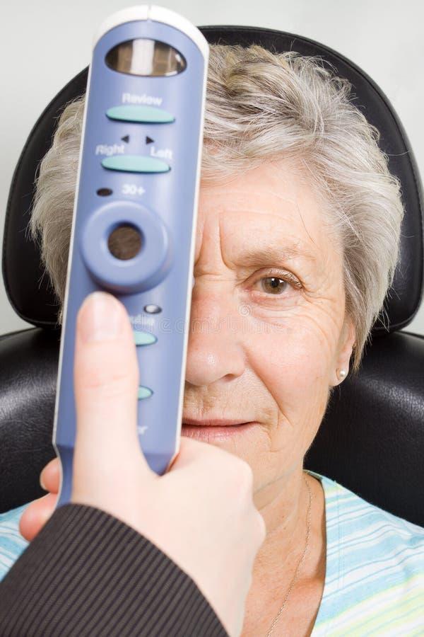 Lady having eye test examination. An older lady taking an eyesight test examination at an optician clinic royalty free stock photos