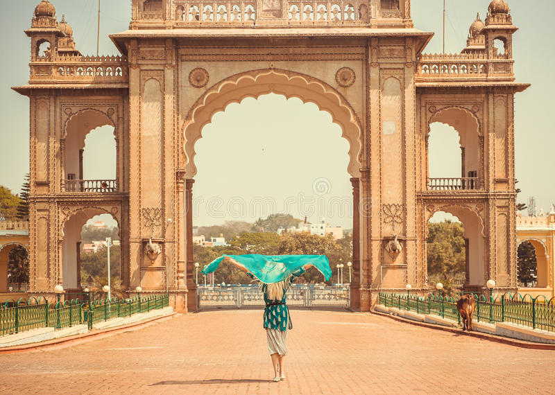 Lady with headscarf going to the indian landmark - Historical gates of Royal Palace of Mysore in Karnataka, India. Lady with headscarf going to the indian stock images