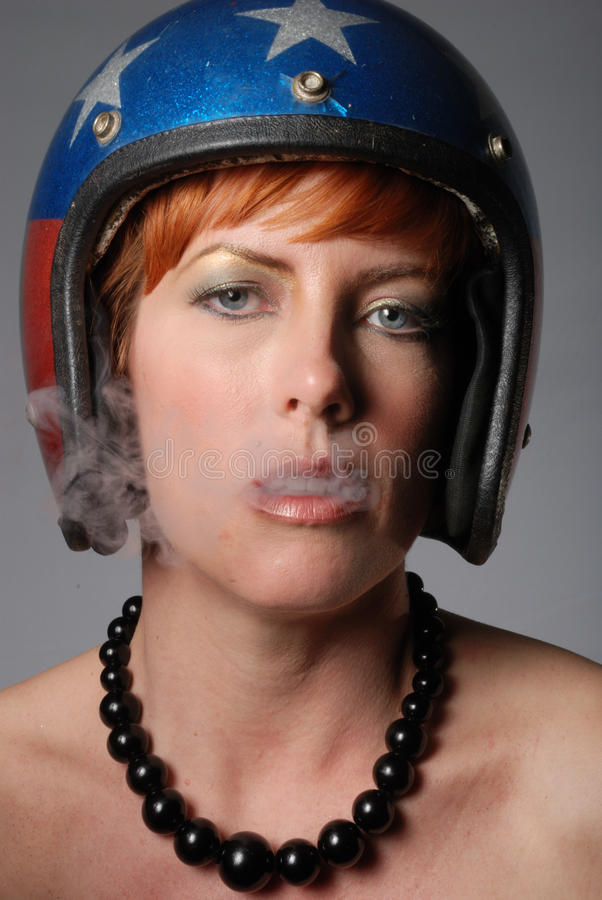 Lady with helmet blowing smoke. Through mouth stock image