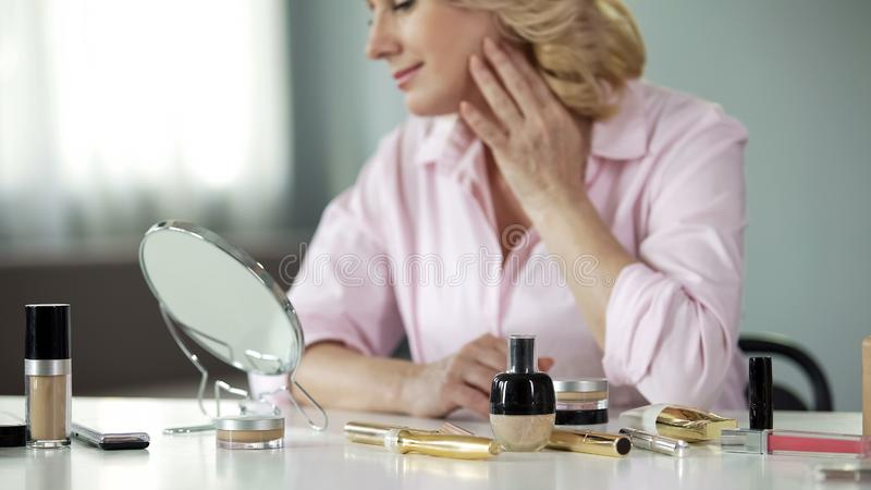 Lady in her 50 satisfied with skin condition after using anti-aging cosmetics. Stock photo royalty free stock photography