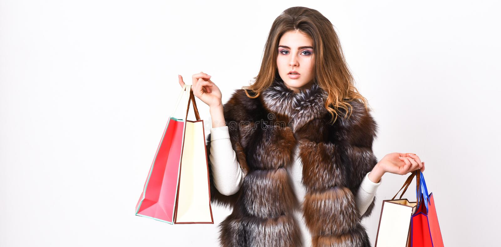 Lady hold shopping bags. Discount and sale. Fashionista buy clothes on black friday. Girl makeup furry coat shopping. White background. Shopping or birthday stock photo
