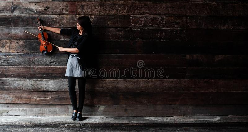 The lady is hold violin and extended right arm ,left hand hold bow ant raise to touch the string stock photo