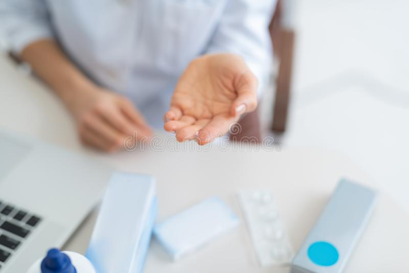 Lady holding transparent contact lens on blurred background. Improve your vision. Close up top view picture of female hand demonstrating contact lens for eyes royalty free stock images