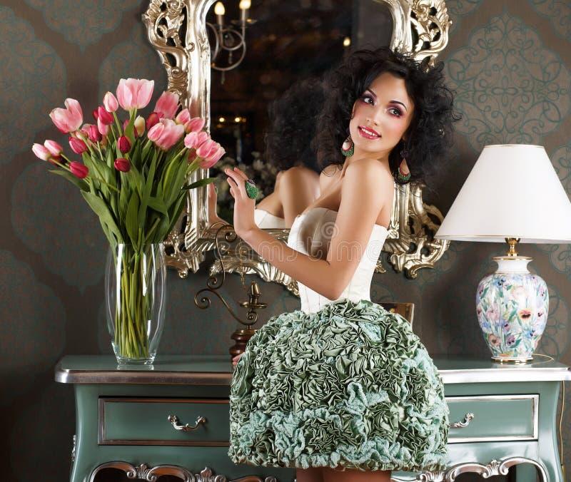 Härlig glamorös kvinna i Retro inre med vasen av blommor. Reflexion arkivfoton