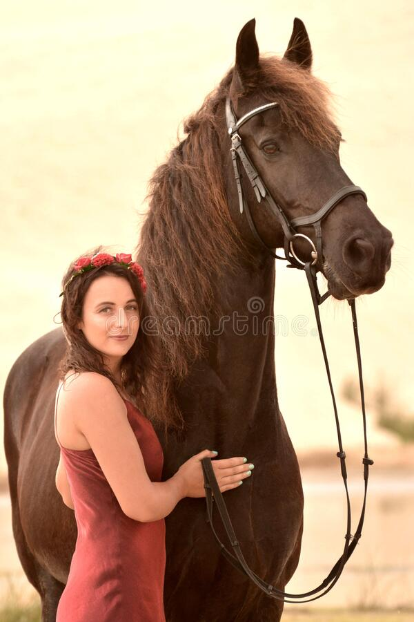 Free Lady In Red With Her Black Horse Royalty Free Stock Image - 181386606